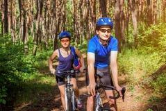骑一辆自行车的夫妇在森林里 库存图片