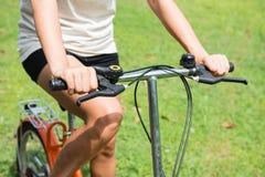 骑一辆自行车的妇女在公园 免版税图库摄影