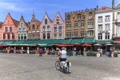 骑一辆自行车的妇女在布鲁日集市广场有偶象色的大厦的在背景 库存图片