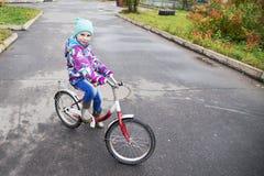 骑一辆自行车的小女孩在秋天公园 免版税库存图片