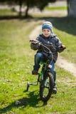 骑一辆自行车的小男孩在公园 免版税库存照片