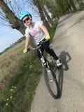 骑一辆自行车的少女在波兰乡下 免版税库存图片