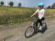 骑一辆自行车的少女在波兰乡下 库存照片