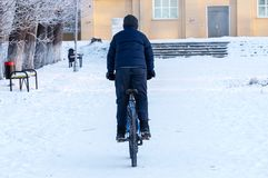 骑一辆自行车的少年在黑暗的衣裳的冬天在白雪背景  免版税库存照片