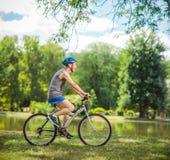 骑一辆自行车的快乐的资深骑自行车的人在公园 免版税库存图片