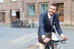 骑一辆自行车的时髦的种族人在城市 免版税库存照片