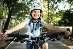 骑一辆自行车的男孩在公园 免版税库存照片
