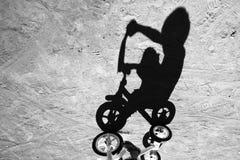 骑一辆自行车的男孩的阴影在巴厘岛印度尼西亚村庄  免版税图库摄影
