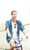 骑一辆自行车的英俊的行家在老镇 旅行, holida 免版税库存照片