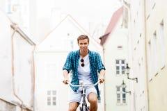 骑一辆自行车的英俊的行家在老镇 免版税库存图片