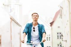 骑一辆自行车的英俊的行家在老镇 库存照片