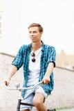 骑一辆自行车的英俊的行家在老镇 免版税库存照片