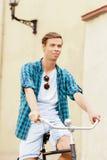 骑一辆自行车的英俊的行家在老镇 免版税图库摄影