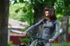 骑一辆自行车的骑自行车者妇女在公园 库存图片
