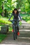 骑一辆自行车的骑自行车者妇女在公园 免版税库存图片