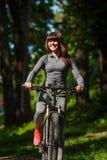 骑一辆自行车的骑自行车者妇女在公园 免版税库存照片