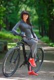 骑一辆自行车的骑自行车者妇女在公园 图库摄影