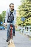 骑一辆自行车的年轻成人人在城市 免版税库存图片