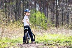 骑一辆自行车的年轻男孩在森林里 库存照片