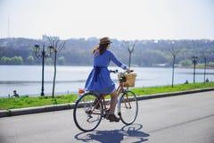 骑一辆自行车的年轻美丽的妇女在公园 活跃人民 图库摄影