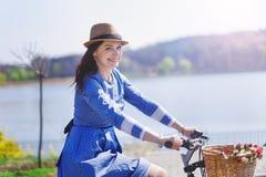 骑一辆自行车的年轻美丽的妇女在公园 活跃人民 库存照片