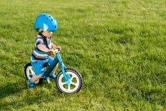 骑一辆蓝色平衡自行车的盔甲的男孩跑自行车 库存图片
