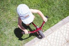 骑一辆蓝色平衡自行车的蓝色焰晕的男孩 免版税图库摄影