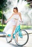 骑一辆蓝色自行车的美丽的女性在一个晴天 图库摄影