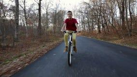 骑他的自行车的十几岁的男孩在晴朗的秋天森林公路-踩的踏板 股票录像