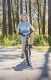骑他的自行车的活跃,健康男孩户外在一个晴天 库存照片