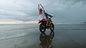 骑减速火箭的摩托车的年轻美丽的夫妇行家在海滩、室外画象、乘坐的人和女孩,旅行 股票视频