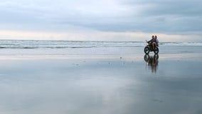 骑减速火箭的摩托车的年轻美丽的夫妇行家在海滩、室外画象、乘坐的人和女孩,旅行 影视素材