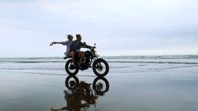 骑减速火箭的摩托车的年轻美丽的夫妇行家在海滩、室外画象、乘坐的人和女孩,旅行 股票录像
