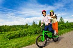 骑同样自行车的微笑的非洲男孩和女孩 免版税库存照片