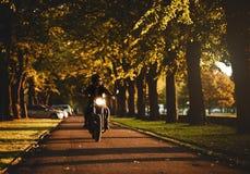 骑咖啡馆竟赛者摩托车的人 免版税库存照片
