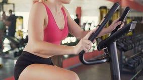骑在健身房、健身和健康生活方式的女运动员固定式自行车 股票录像