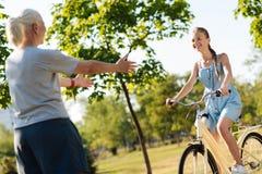 骑在她的祖母前面的正面小女孩一辆自行车 免版税库存照片