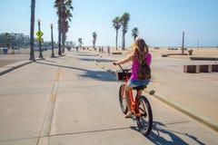 骑在威尼斯海滩下的年轻美丽的女孩一辆自行车 免版税库存图片