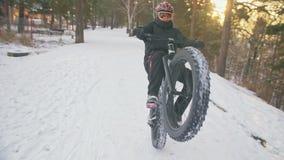 骑在室外的专业极端运动员骑自行车的人肥胖自行车 在冬天雪森林人的骑自行车者乘驾试验 股票录像