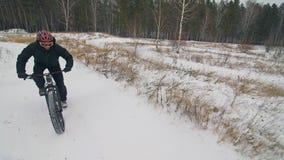 骑在室外的专业极端运动员骑自行车的人肥胖自行车 在冬天雪森林人的骑自行车者乘驾试验 股票视频