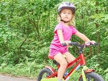 骑在室外的愉快的孩子一辆自行车 图库摄影