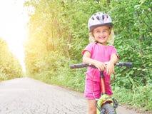 骑在室外的愉快的孩子一辆自行车 库存图片