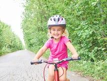 骑在室外的愉快的孩子一辆自行车 免版税库存照片