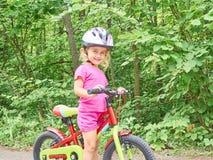 骑在室外的愉快的孩子一辆自行车 库存照片