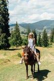 骑在山的可爱的女孩一匹马 库存图片