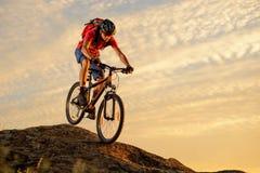骑在岩石下的红色的骑自行车者自行车在日落 极端体育和Enduro骑自行车的概念 免版税图库摄影