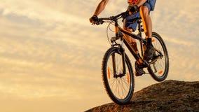 骑在岩石下的骑自行车者自行车在日落 极端体育和Enduro骑自行车的概念 库存照片