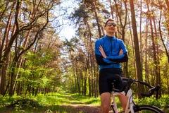 骑在春天森林人的年轻人自行车骑士一辆路自行车有休息 免版税库存图片