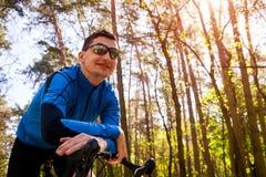 骑在春天森林人的愉快的年轻人自行车骑士一辆路自行车有休息 库存图片