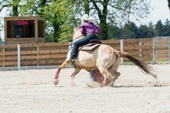 骑在桶赛跑的事件的年轻女牛仔一匹美丽的油漆马在圈地 图库摄影